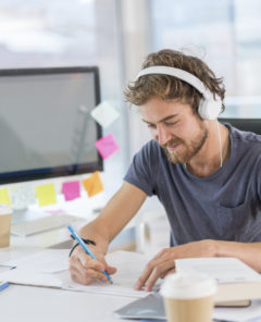 Young graphic designer working at the office and listening to music wearing headphones